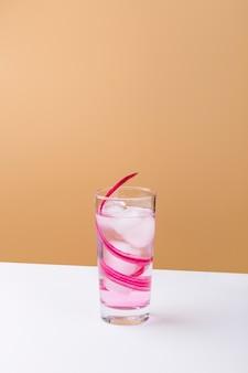 Вкусный розовый напиток с кубиками льда на белом столе