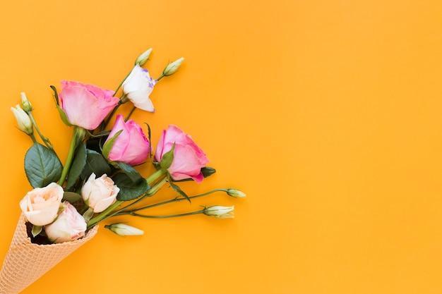 オレンジ色のコピースペース背景にトップビューバラの花束
