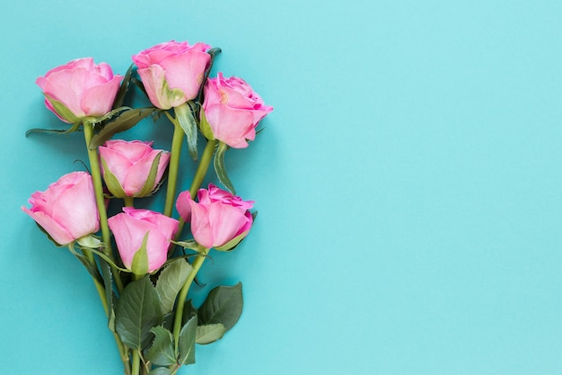 青いコピースペース背景にトップビューバラの花束