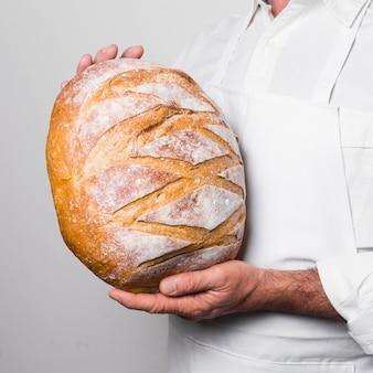 Шеф-повар в белой одежде держит теплый хлеб