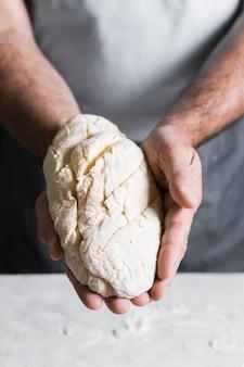 Мужчина держит тесто для хлеба вид спереди