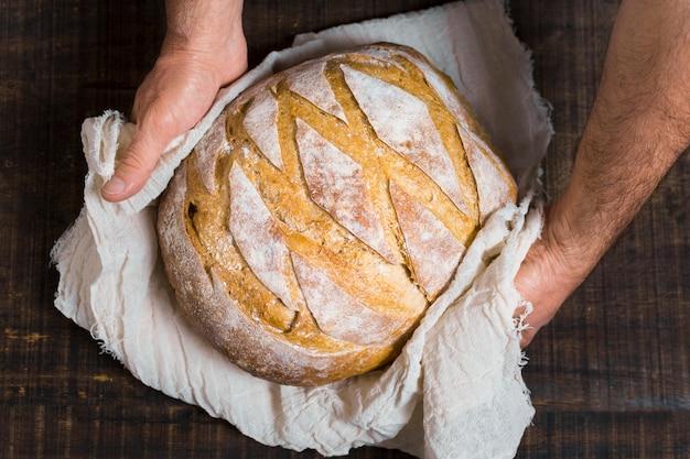 Руки держат вкусный хлеб, завернутый в ткань
