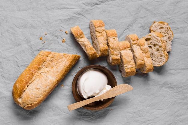 Сметана в миске и ломтики хлеба