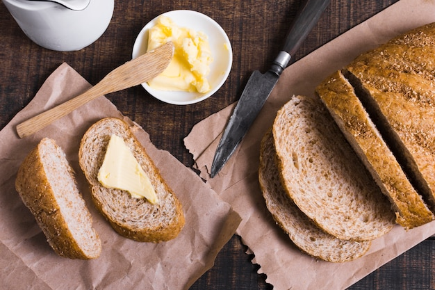 Вид сверху ломтики хлеба с маслом и ножом