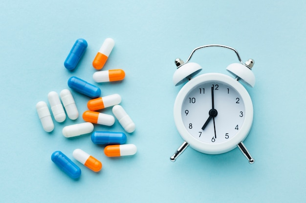 トップビューのカラフルな錠剤と白い時計