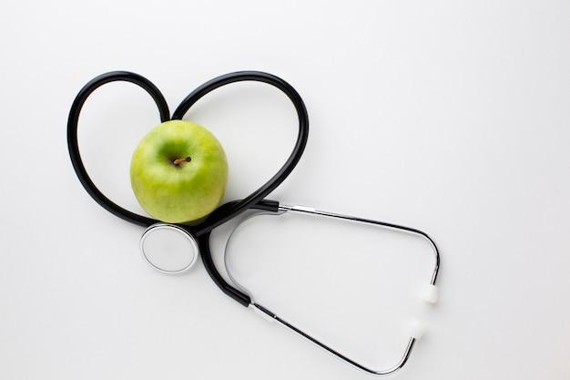 Плоский лежал зеленое яблоко и стетоскоп