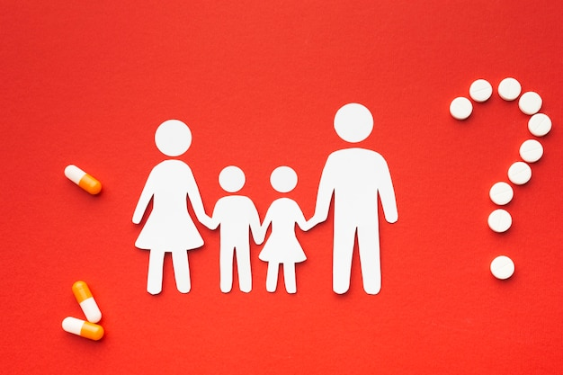 錠剤の形をした疑問符の付いた段ボール家族形