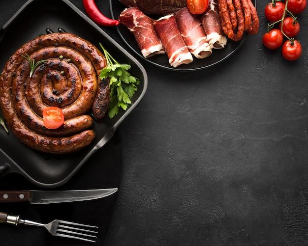 Вид сверху жареная колбаса со столовыми приборами на столе