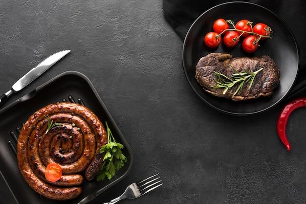 Вид сверху жареная колбаса и вкусный стейк готовые к употреблению