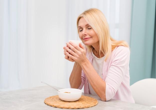Портрет счастливой старшей женщины, где подают завтрак