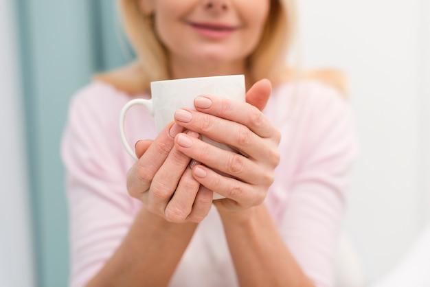 Макро взрослая женщина, держа чашку кофе
