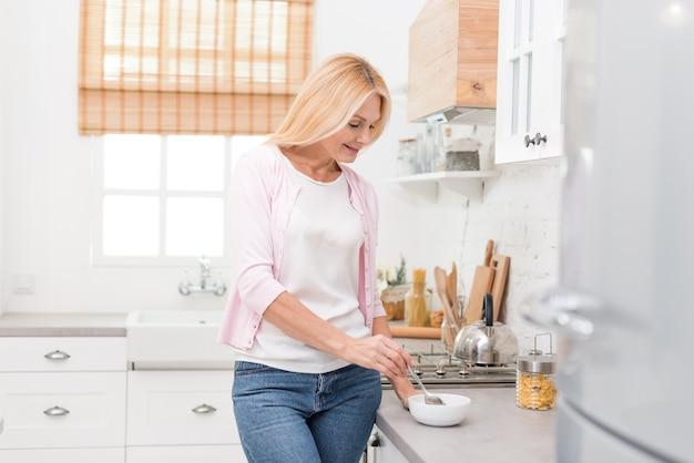 Портрет милой старшей женщины, имеющей завтрак