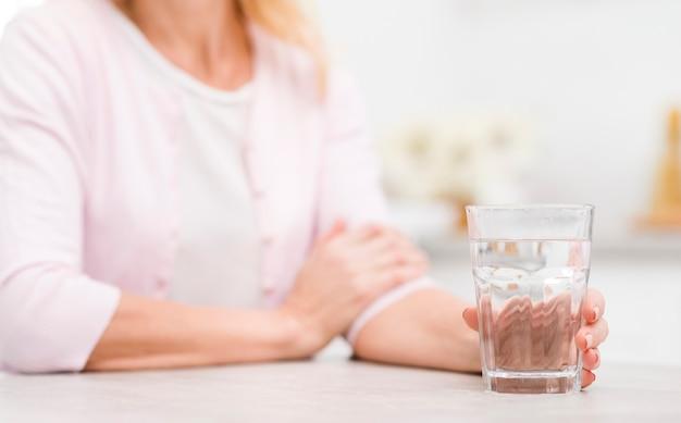 Крупным планом зрелая женщина, держащая стакан воды