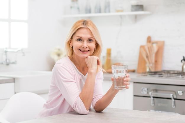 水のガラスを保持している美しい女性の肖像画