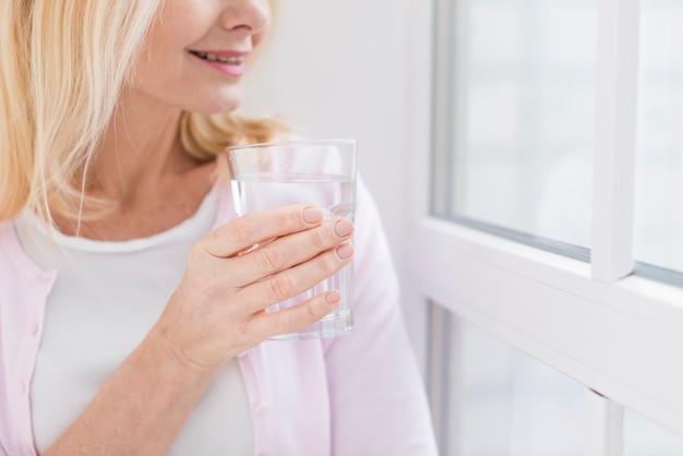 水のガラスとクローズアップの年配の女性
