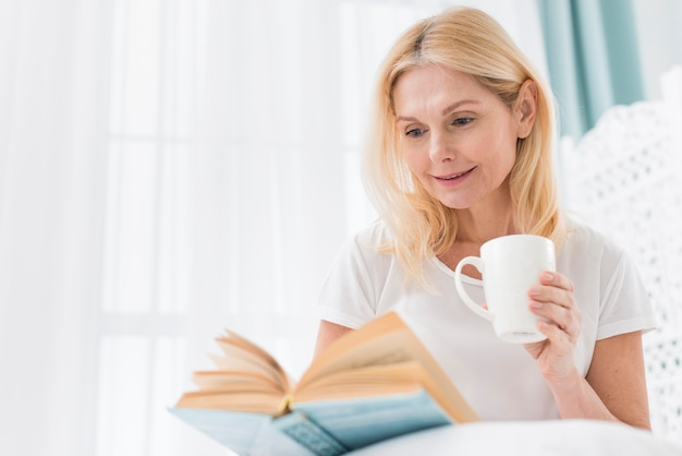 Портрет старшей женщины читая книгу в кровати