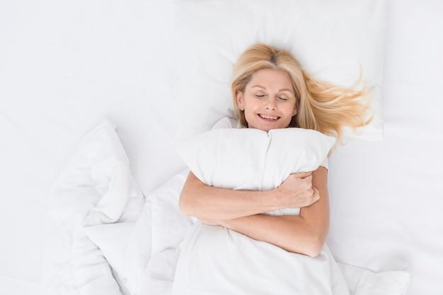 Портрет красивой старшей женщины, держащей подушку