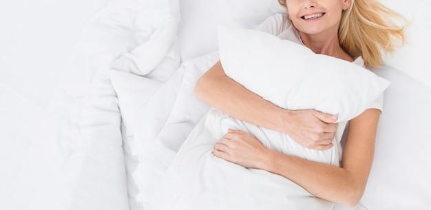 彼女の枕を保持しているクローズアップのかなり成熟した女性