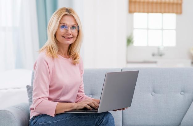 Портрет красивой старшей женщины работая от дома