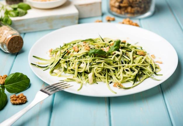 Высокий вид салат с вилкой на деревянный стол