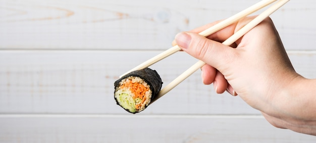 Рука держит палочки для еды и суши ролл
