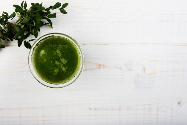 コピースペースを持つガラスの自然な緑のスムージー