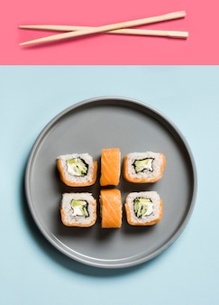 Расположение суши роллов с палочками для еды и соевым соусом