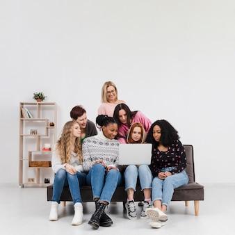 Группа женщин, глядя вместе через ноутбук