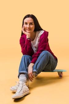 スケートボードの上に座って美しい女性
