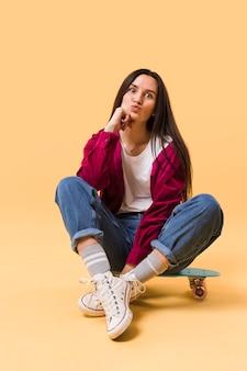 スケートボードの上に座ってかわいいモデル