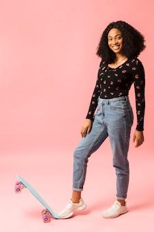 スケートボードのスタジオショットで幸せな女