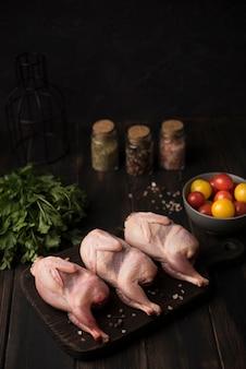 Высокий угол сырой курицы на деревянной доске с ингредиентами и приправами