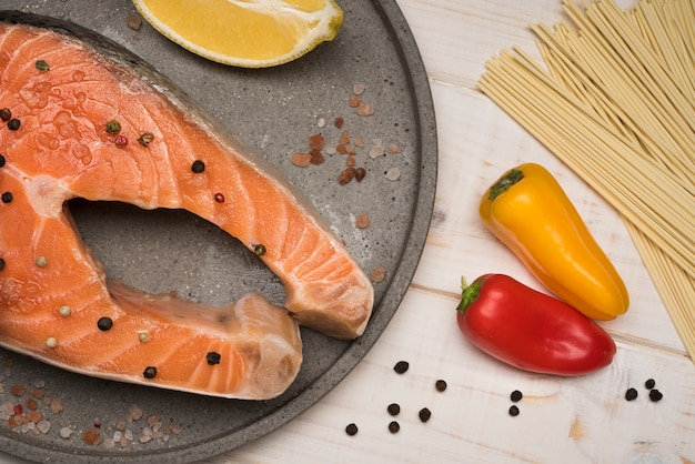 Вид сверху стейк из лосося на подносе с перцем