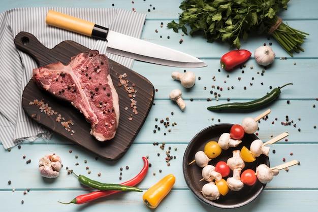 Плоский сырой стейк на косточке с ингредиентами