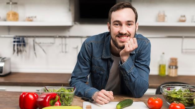 Середине выстрел мужчины, улыбаясь в кухне