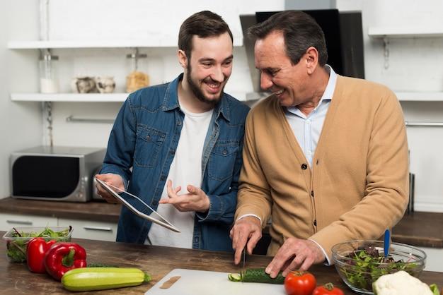 父と息子が台所でサラダを作る