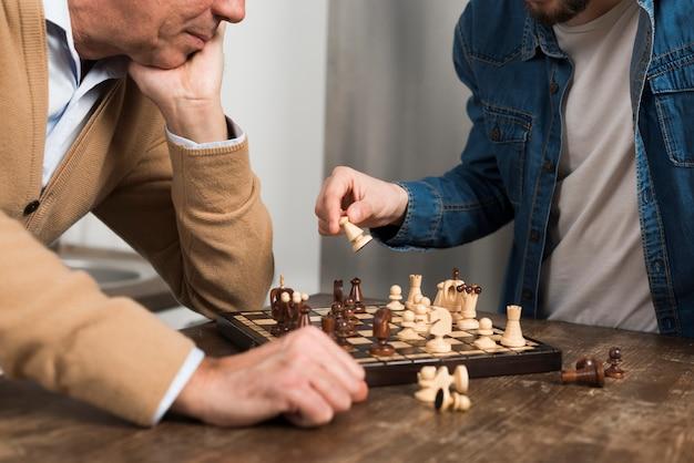 Крупным планом сын и отец играют в шахматы