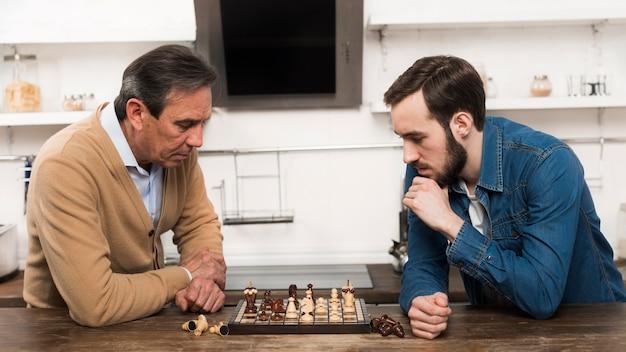Сын и папа играют в шахматы на кухне