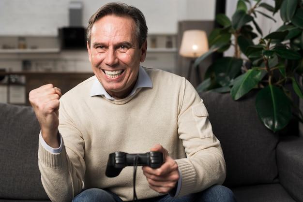 Счастливый старик играет в видеоигру