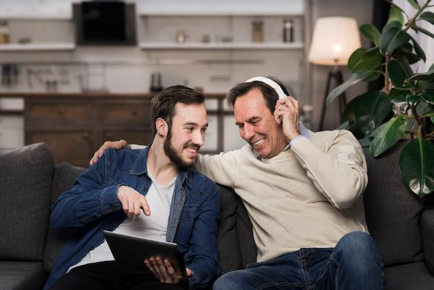 Отец и сын смеются и глядя на планшет