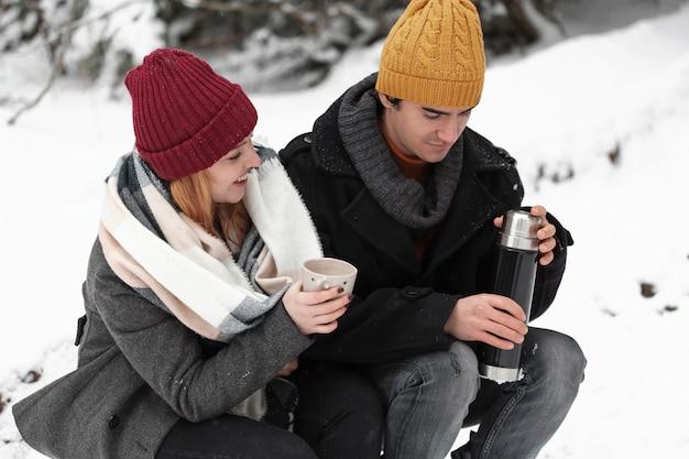 座っているカップルと熱い飲み物を飲む