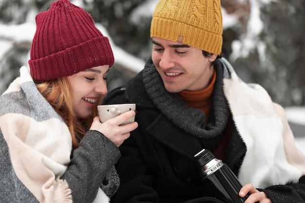 Пара с зимней одеждой проводит время на свежем воздухе
