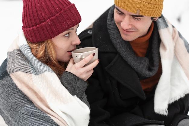 お茶を飲む冬の服をカップルします。