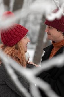 カップルがお互いを見て雪の冬のシーズン
