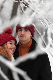 公園でカップルと雪に覆われた冬のシーズン
