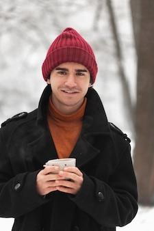 赤い帽子をかぶっているとお茶のカップを保持しているスマイリー男