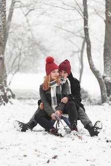 冬の日光の下でそりに座っている若いカップル