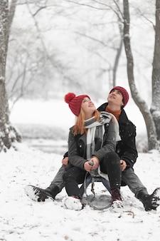 Молодая пара сидит на санях