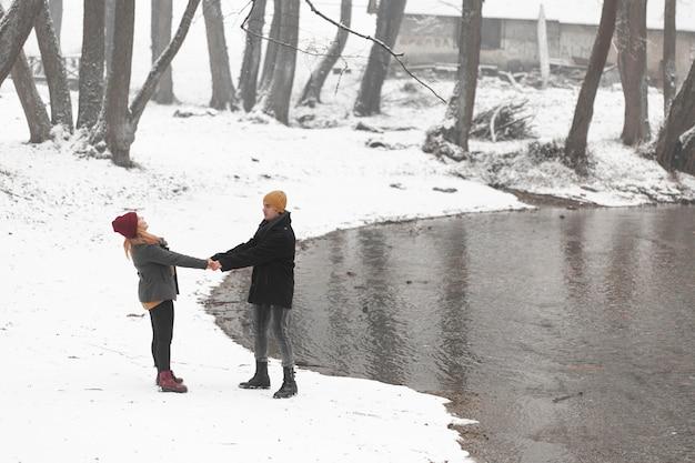 川の横に手を繋いでいる若いカップル