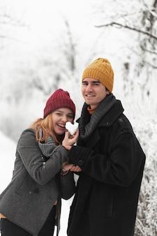 雪から作られたハート形を保持しているカップル